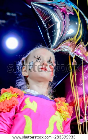 Head and Shoulders Portrait of Young Blond Girl Wearing Clown Make Up and Costume Holding Star Shaped Balloon on Stage in front of Red Curtain #283595933