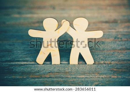 Wooden little men holding hands on wooden boards background. Symbol of friendship, love and teamwork Royalty-Free Stock Photo #283656011