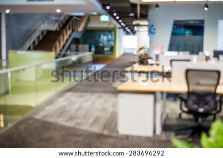 Abstract blur business office working space background with modern interior with table and chair with devices. Blurry creative workplace design background