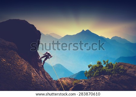 Silhouette of climber on a cliff against beautiful sunset in a high mountains #283870610