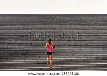 sporty woman working out running up stairs outdoors for morning workout Royalty-Free Stock Photo #283995188