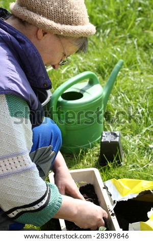 A woman potting soil in spring. #28399846