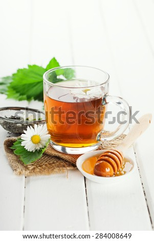Herbal tea in a glass bowl with camomile flowers and honey on white rustic wooden background, selective focus #284008649