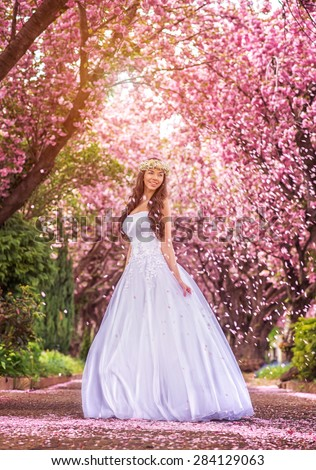Beautiful bride in a white dress under the sakura tree and flower petals #284129063