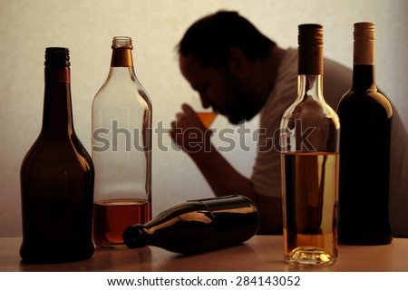 silhouette of anonymous alcoholic person drinking behind bottles of alcohol  Royalty-Free Stock Photo #284143052