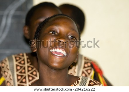 LAKE NKURUBA, UGANDA - AUGUST 28, 2010: Close up of an unidentified happy teenager sings and dances a traditional performance in the Nkuruba Culture Entertainment Club.  #284216222