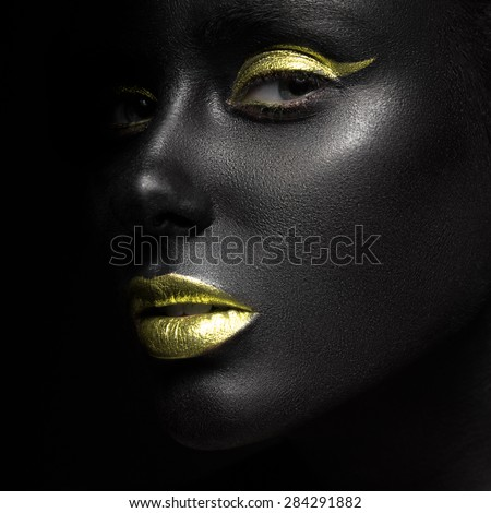 fashion portrait of a dark-skinned girl with color make-up.Beauty face. Picture taken in the studio on a black background.