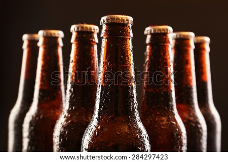 Glass bottles of beer on dark background Royalty-Free Stock Photo #284297423