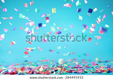 Colored confetti flying on blue background Royalty-Free Stock Photo #284495933