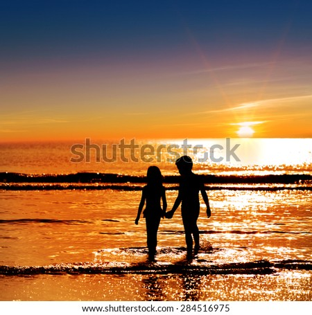 Silhouette boy holding  girl hand on the sea against the strong sunrise #284516975