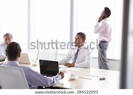 Four Businessmen Having Meeting Around Boardroom Table #284522093