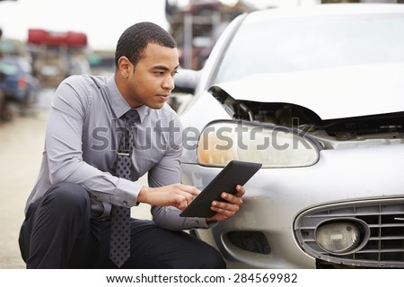 Loss Adjuster Using Digital Tablet In Car Wreck Inspection #284569982