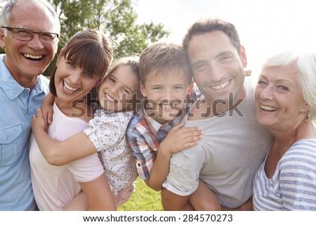 Multi Generation Family Giving Children Piggybacks Outdoors Royalty-Free Stock Photo #284570273