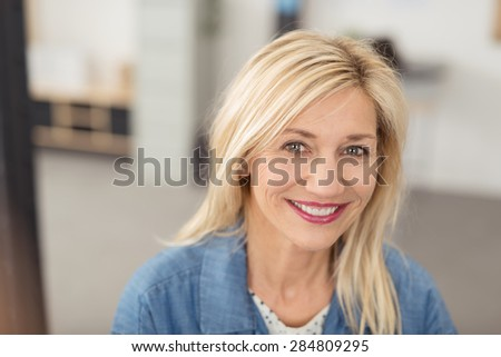 Long-haired blond woman with a joyful facial expression smiling at camera with blue eyes and white teeth, portrait indoors #284809295