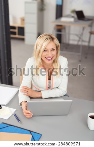 Happy Blond Businesswoman Sitting at the Table with Laptop Computer and Looking Into Distance in High Angle View. #284809571