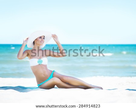 Gorgeous and beautiful young girl relaxing on a summer beach #284914823