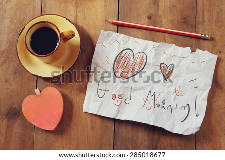 top view image of paper with the text good morning next to coffee cup and wooden heart shape
