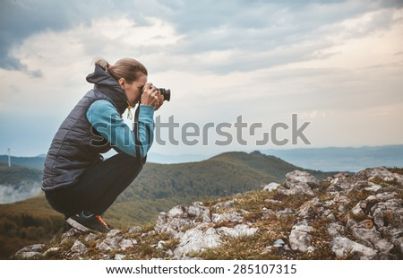 Woman photographer is taking a picture of mountain landscape
