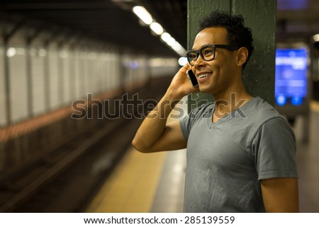 Young African Asian man in New York City in subway station talking on cell phone #285139559