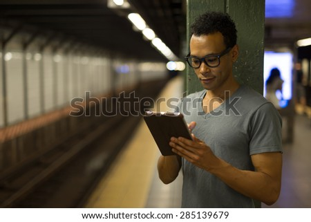 Young African Asian man in New York City in subway station using tablet pc  #285139679