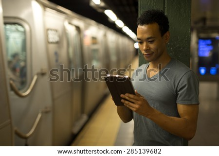 Young African Asian man in New York City in subway station using tablet pc  #285139682