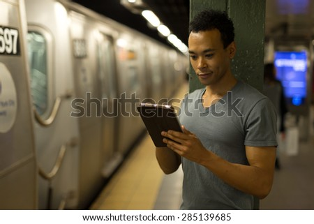 Young African Asian man in New York City in subway station using tablet pc  #285139685