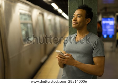 Young African Asian man in New York City in subway station texting cell phone #285140006