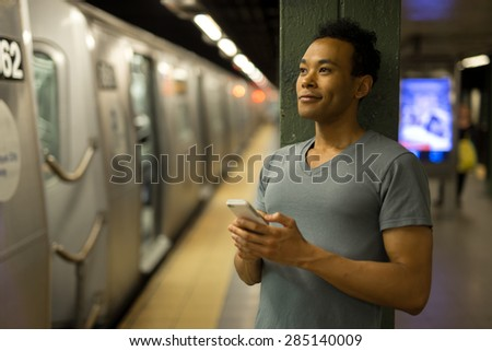 Young African Asian man in New York City in subway station texting cell phone #285140009