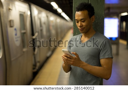 Young African Asian man in New York City in subway station texting cell phone #285140012