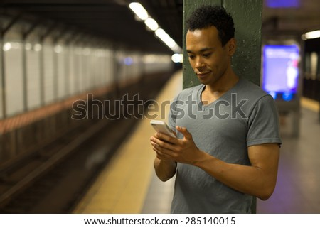 Young African Asian man in New York City in subway station texting cell phone #285140015