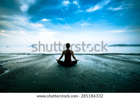 Silhouette young woman practicing yoga on the beach #285186332