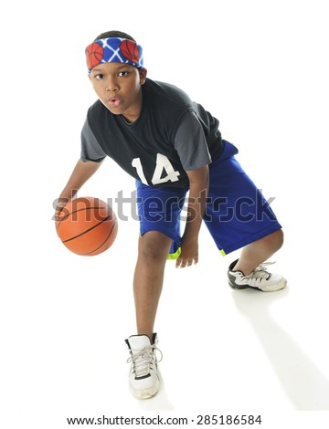An African American tween basketball player actively dribbling his ball.  On a white background. #285186584