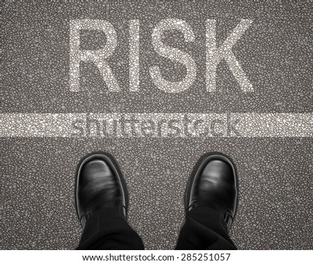 Take a risk concept with feet on road behind white line #285251057