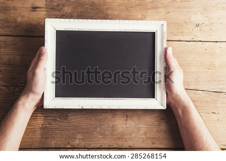 Hands of the father holding white picture frame on wooden floor background.