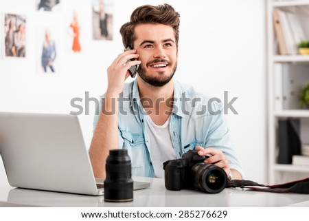Enjoying creative work. Happy young man talking on the mobile phone and smiling while sitting at his working place and holding digital camera #285276629