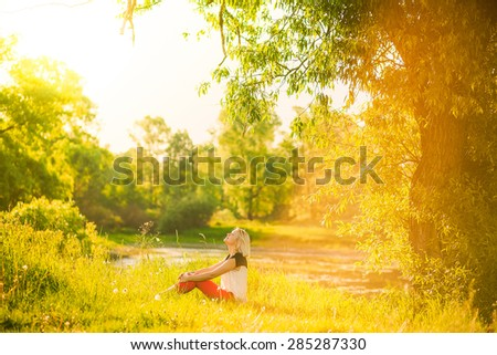 beautiful woman having rest under huge tree in sunset time outside. Sunset people. Lonely woman enjoying nature landscape in evening. Summer or spring day. Girl sitting on grass Color horizontal image #285287330
