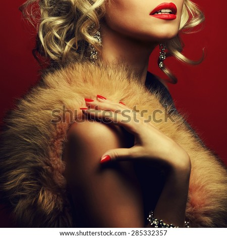 Girl's best friends and femme fatale concept. Marilyn Monroe style. Portrait of rich young woman wearing expensive luxurious diamond accessories, furs. Studio shot
