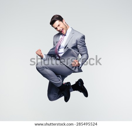 Funny cheerful businessman jumping in air over gray background #285495524