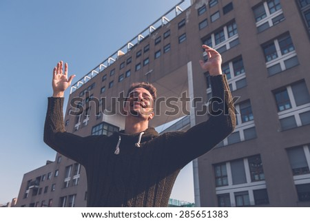 Young handsome man with short hair posing in an urban context #285651383