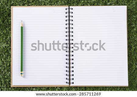 notebook paper background with pencil on green grass background  #285711269