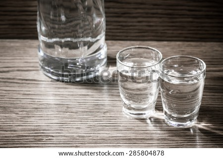 Vodka shots filled with alcohol on wooden bar. #285804878