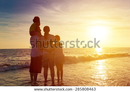happy family watching the sunset on the beach #285808463