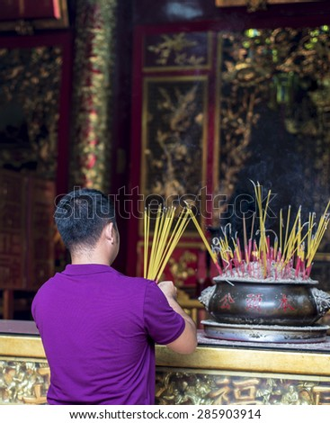 Ho Chi Minh City, Vietnam 24 May 2015: A man visiting Ong Bon Pagoda, place smoking incense sticks into an urn at the Ong Bon Pagoda. The incense is lit as an offering to the gods. #285903914