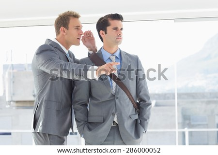 Businessman telling secret to his colleague in the office #286000052