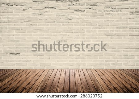 Old interior room with abstract light beige brick wall pattern and brown wood floor #286020752