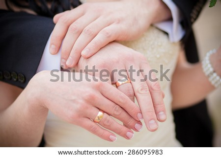 Wedding  gold rings on the hands of the bride and groom #286095983