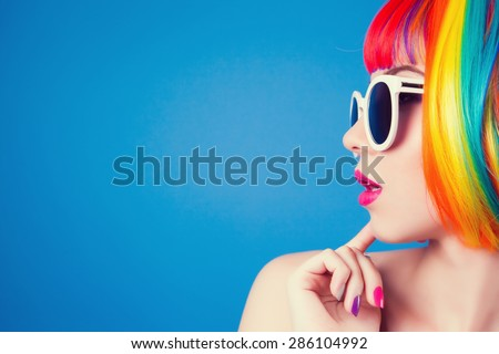 beautiful woman wearing colorful wig and white sunglasses against blue background Royalty-Free Stock Photo #286104992