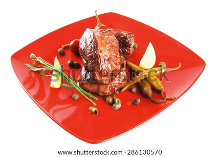 roast beef meat fillet medallion with cherry tomatoes and hot peppers on red plate isolated on white background #286130570