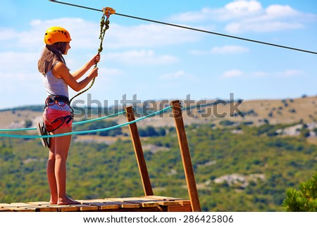 young woman are ready to descend on zipline in mountain, extreme sport #286425806
