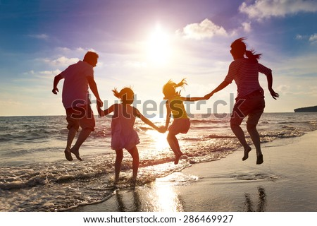 happy family jumping together on the beach Royalty-Free Stock Photo #286469927